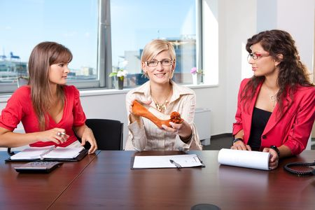 Young businesswomen holding a shoe in hand during a creative meeting. photo