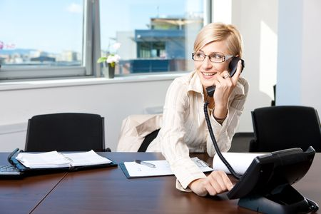 businesspersons: Young businesswoman sitting at desk in office, talking on landline phone, smiling.