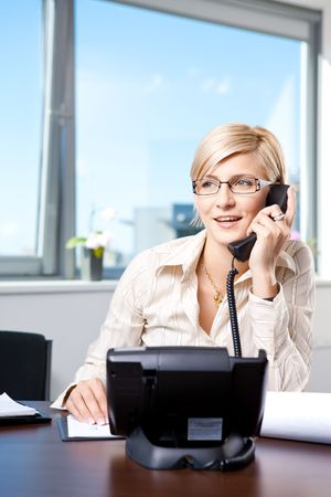Young businesswoman sitting at desk in office, talking on landline phone, smiling. photo