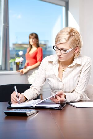 well read: Young businesswoman sitting at desk in office, writing notes to personal organizer.
