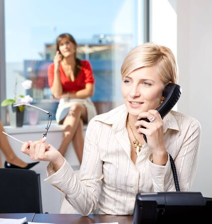 office wear: Young businesswoman sitting at desk in office, talking on landline phone, smiling.