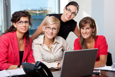 Team of  young businesswomen using laptop computer  in meeting room. Looking at camera, smiling. photo