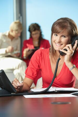 clothes organizer: Young businesswoman sitting at desk in office, talking on landline phone, smiling.