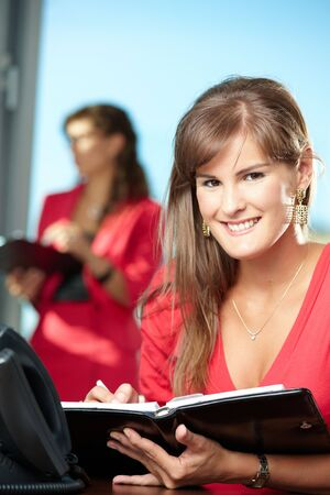 Closeup portrait of young businesswoman writing notes into personal organizer, smiling. photo
