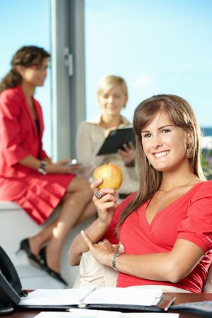 Portrait of attractive young businesswoman holding apple, smiling. photo