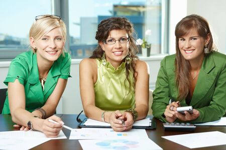 Group of attractive businesswomen sitting at meeting room, discussing financial charts on table, smiling.