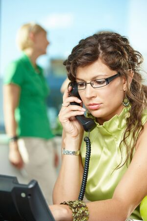 Young businesswoman sitting at desk in office, listening on landline phone. photo