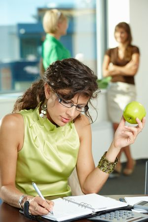 Young businesswoman sitting at desk in office, writing notes into personal organizer, holding apple. photo