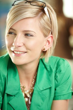 Closeup portrait of attractive young businesswoman wearing green shirt, smiling. photo