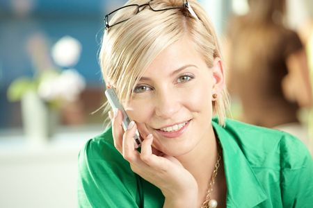 Young businesswoman sitting at desk in office, talking on mobile phone, smiling. photo