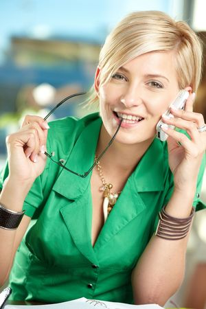 Young businesswoman sitting at desk in office, talking on mobile phone, smiling. Stock Photo - 5742004