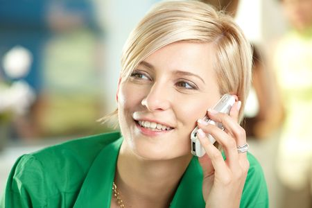Young businesswoman sitting at desk in office, talking on mobile, smiling. photo