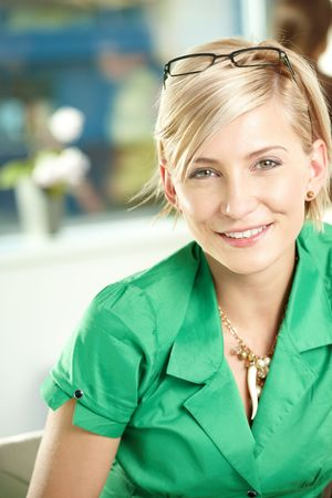 casual office: Closeup portrait of attractive young businesswoman wearing green shirt, smiling.
