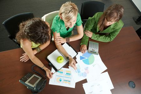 finacial: Young businesswomen sitting at table in meeting room, discussing finacial charts. Overhead shot.