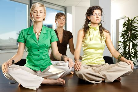 Young businesswomen sitting in yoga position on meeting room table. photo