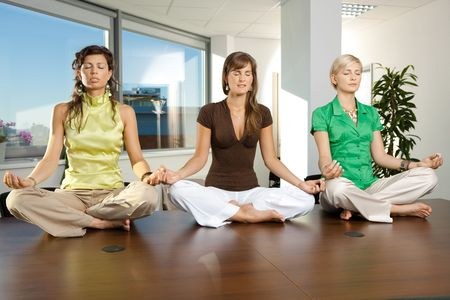 business activity: Young businesswomen sitting in yoga position on meeting room table.