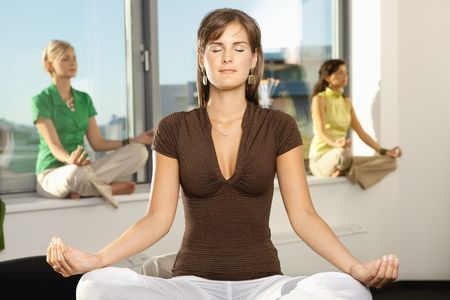 Young businesswomen sitting in yoga position in office. photo