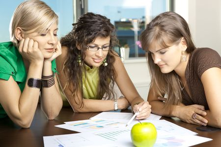 Casual businesswomen leaning on table in meeting room, discussing finacial charts. photo