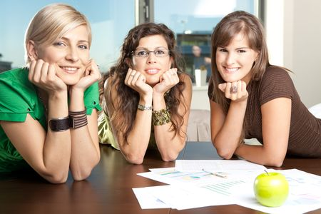Group of attractive businesswomen leaning on hands at meeting room table, smiling. photo
