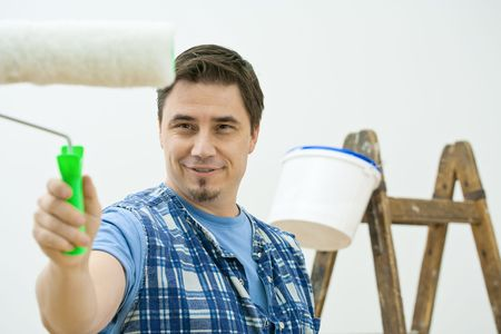 Man doing home improvement, painting with roller. Isolated on white background. photo