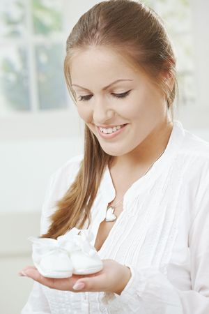 An excited pregnant mother-to-be is holding baby shoes for her new baby. Stock Photo - 5759656