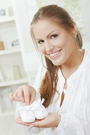 An excited pregnant mother-to-be is holding baby shoes for her new baby.  Stock Photo - 5759493