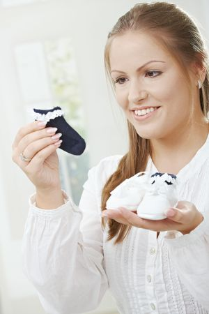 Portrait of pregnant women waiting for the newcomer, holding baby shoe and sock, smiling. Stock Photo - 5759662