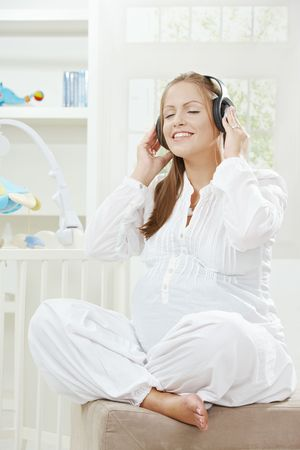 Pregnant woman sitting besides new crib in childrens room, listening music. photo
