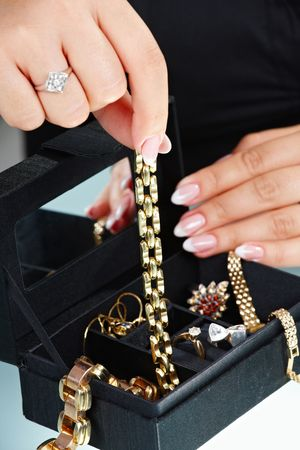 femal: Closeup of femal hand taking out golden bracelet from jewelry box.