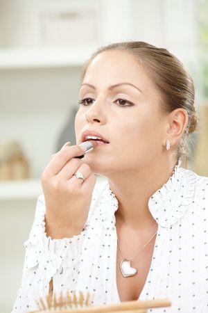 Portrait of beautiful young woman applying lipstick. photo