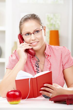 snug: Happy young woman sitting at table talking on landline phone, holding personal organizer. Stock Photo