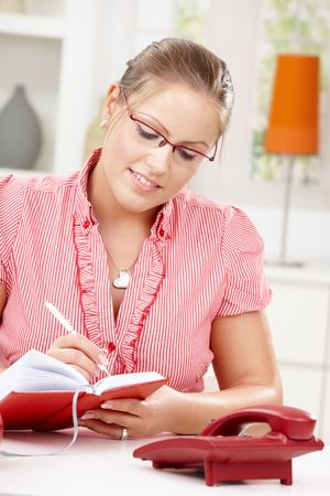 snug: Happy young woman sitting at table writing in diary book, smiling. Stock Photo