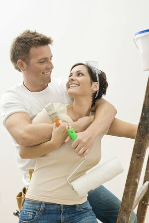 Happy couple doing home improvement. Holding painting tools, hugging and smiling to each other. Stock Photo - 5747169