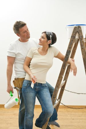 Young couple painting their new home, looking at each other, smiling. photo
