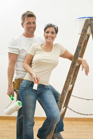copule: Young copule posing with ladder, holding paint roller and brush, smiling. Stock Photo