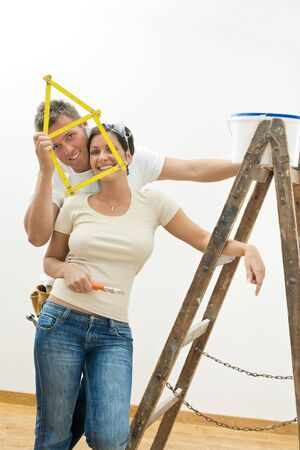 Happy young couple playing with ruler while improving their new home. photo