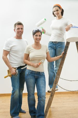 Young people doing home improvement, posing with tools and ladder, smiling. photo