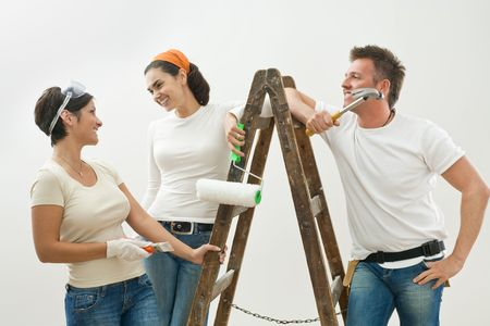 Young couple and friend painting new home, smiling at each other. Isolated on white background. photo
