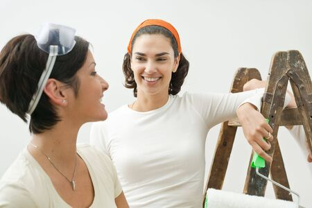 Portrait of young women painting new home, smiling at each other. Isolated on white background. photo