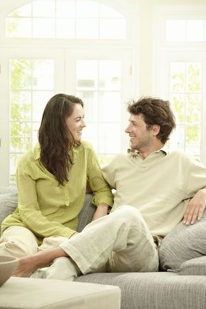 Happy young couple sitting together on couch at home, looking at each other, smiling. Stock Photo - 5754813