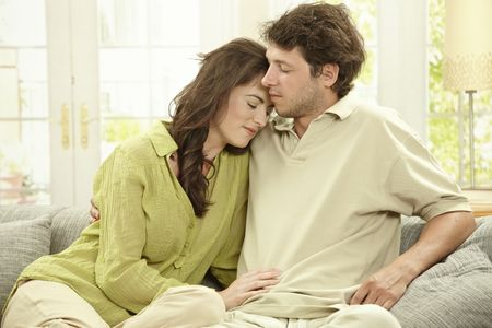 Young couple resting together on couch at home, embracing. photo