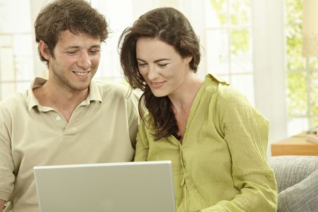 Young couple using laptop computer at home, sitting at couch, looking at screen, smiling. photo
