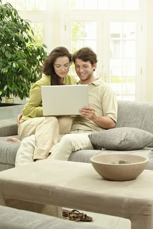 Young couple using laptop computer at home, sitting at couch, smiling. photo