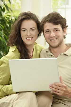 Young couple using laptop computer at home, sitting at couch, looking at camera, smiling. photo