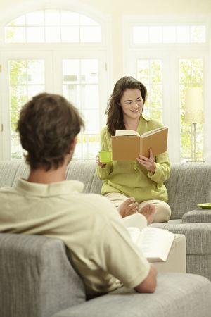 good looking boy: Young  couple reading book sitting at home on couch. Selective focus on women.