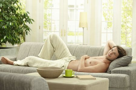 bare chest: Casual bare chested young man resting on couch at home. Stock Photo
