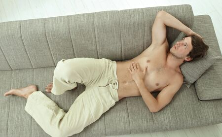 Casual bare chested young man resting on couch at home, high angle shot. photo