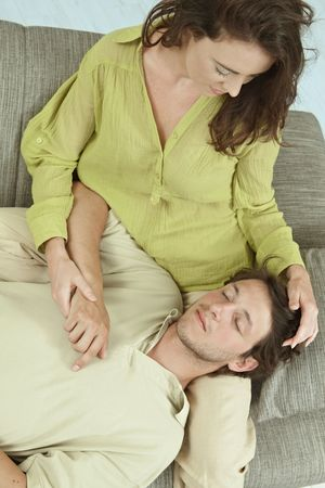 hing: Young couple resting together on couch at home, embracing. Hing angle shot. Stock Photo