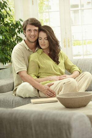 Portrait of happy couple sitting together on couch, embracing, smiling. Stock Photo - 5754811
