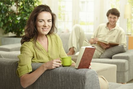 Young  couple reading book sitting on couch in living room. Selective focus on smiling women. photo